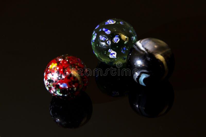 Três mármores coloridos em uma fotografia do close up imagens de stock royalty free