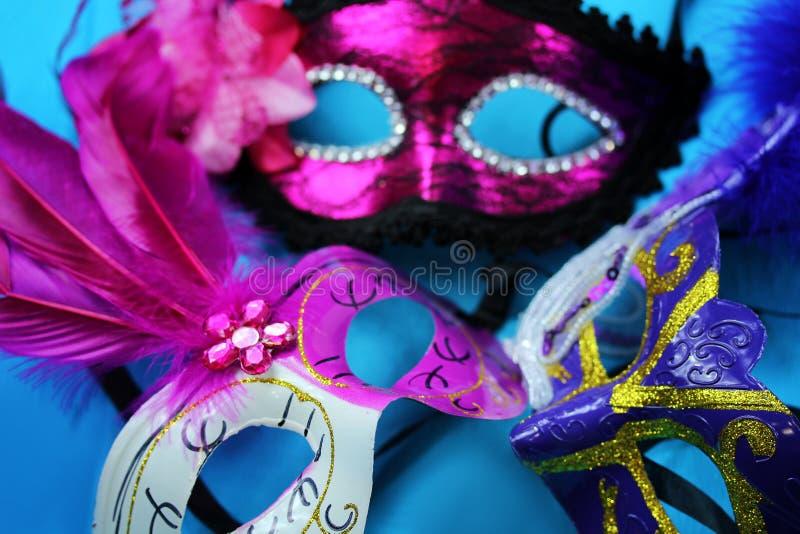 Três máscaras brilhantes do carnaval em um close-up azul do fundo imagens de stock royalty free