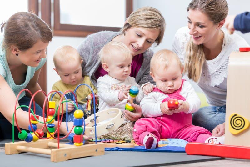 Três mães felizes que olham seus bebês jogar com brinquedos seguros foto de stock royalty free