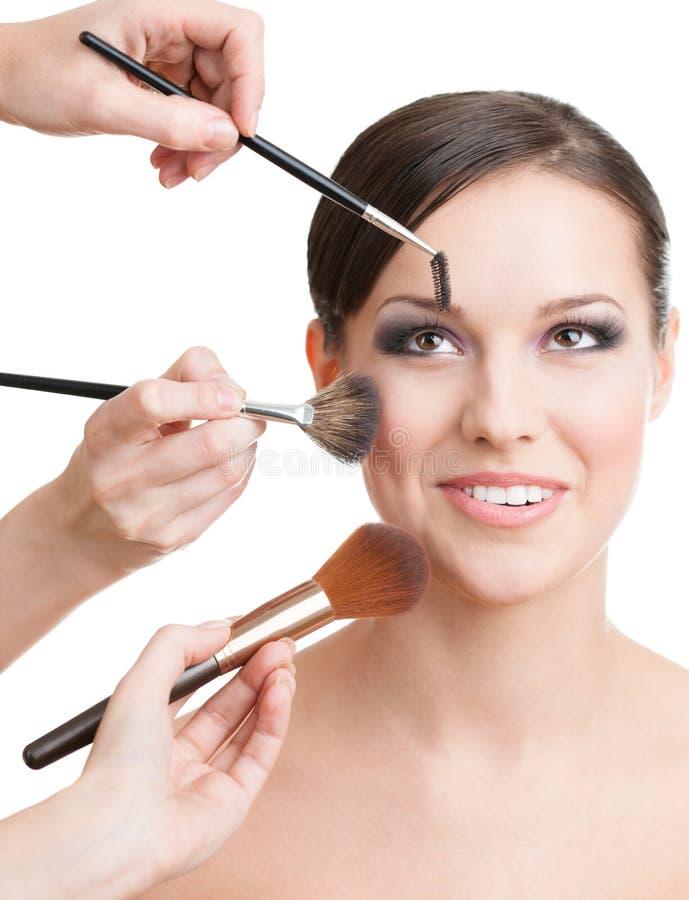 Três mãos que aplicam cosméticos na face da mulher imagens de stock royalty free