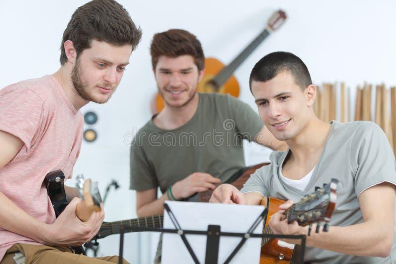 Três músicos masculinos novos que olham a partitura imagens de stock