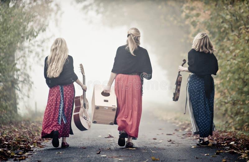 Três músicos na paisagem do outono foto de stock