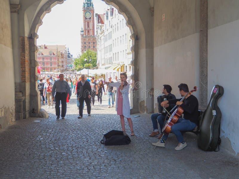 Três músicos que jogam em uma porta velha foto de stock royalty free