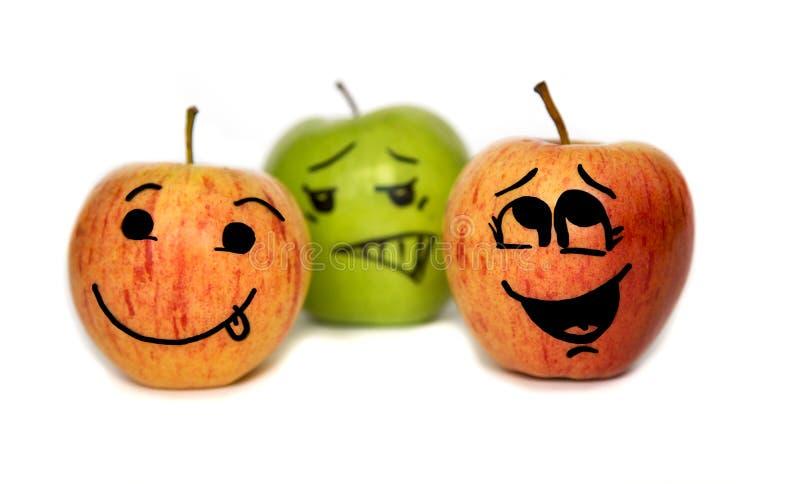 Três maçãs com as caras dos desenhos animados isoladas foto de stock