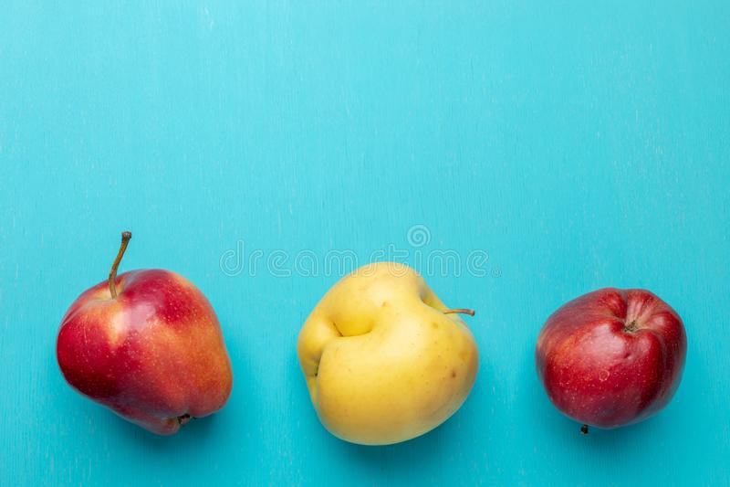 Três maçãs feias estão encontrando-se na linha na parte inferior na turquesa pintaram o fundo de madeira fotografia de stock royalty free