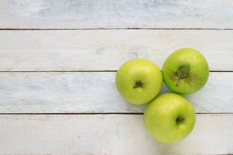 Três maçãs verdes maduras Fruto natural com folhas em uma tabela de madeira branca imagens de stock