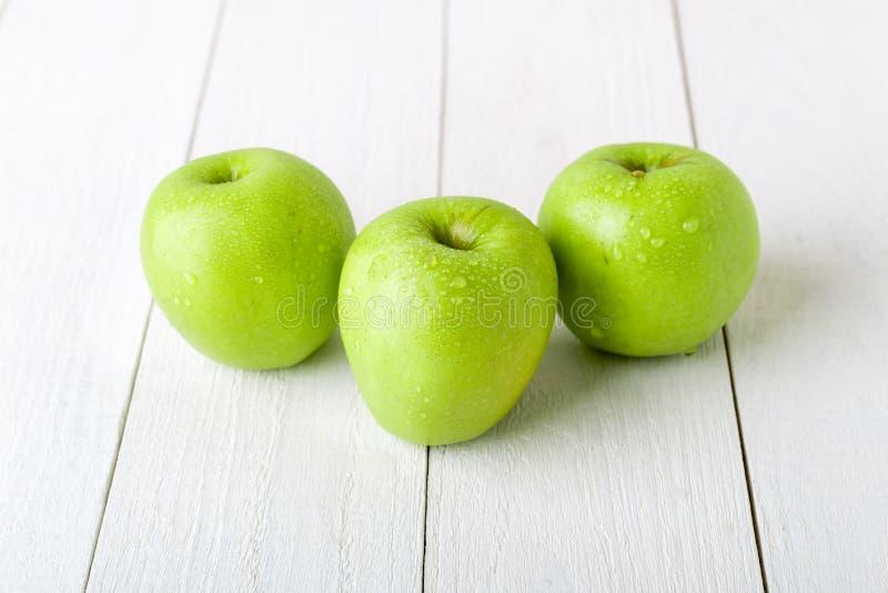 Três maçãs verdes molhadas no fundo de madeira branco Fim acima foto de stock royalty free