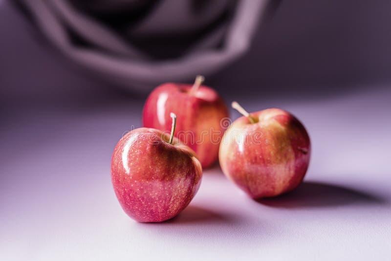 Três maçãs vermelhas bonitas na tabela fotos de stock