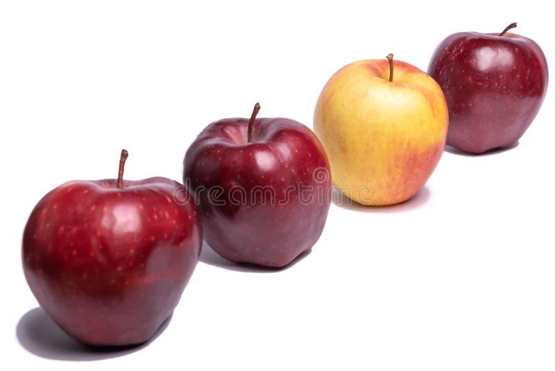 Três maçãs vermelhas e uma maçã amarela foto de stock royalty free