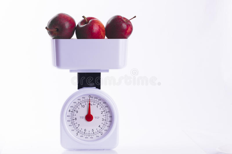 Três maçãs vermelhas em escalas de peso imagem de stock royalty free