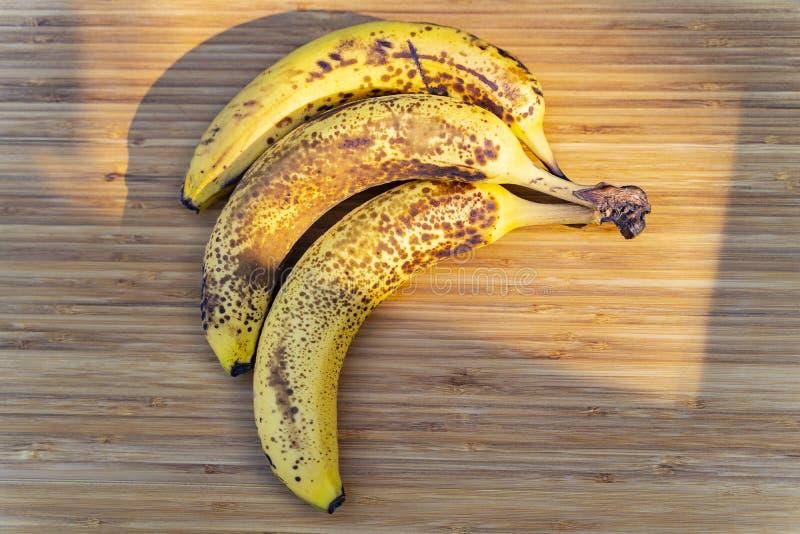 Três mancharam bananas maduras em uma placa de corte de madeira imagem de stock royalty free