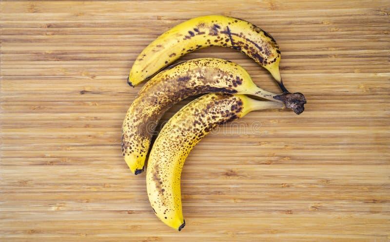 Três mancharam bananas maduras em uma superfície de madeira foto de stock royalty free