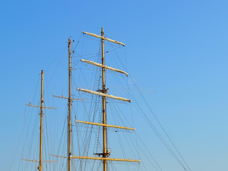 Três mastros de um navio de navigação com dobrado acima das velas e das saias contra um céu azul do verão foto de stock