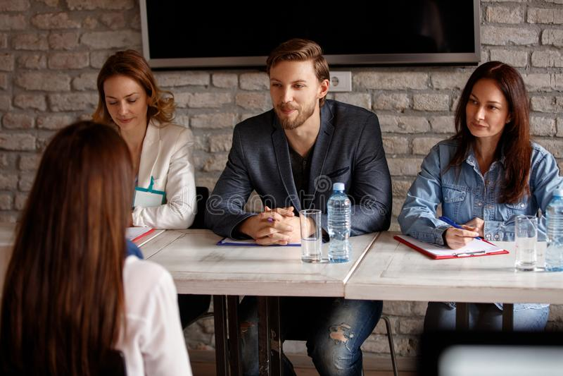 Três membros da comissão do emprego que falam com candidato imagens de stock