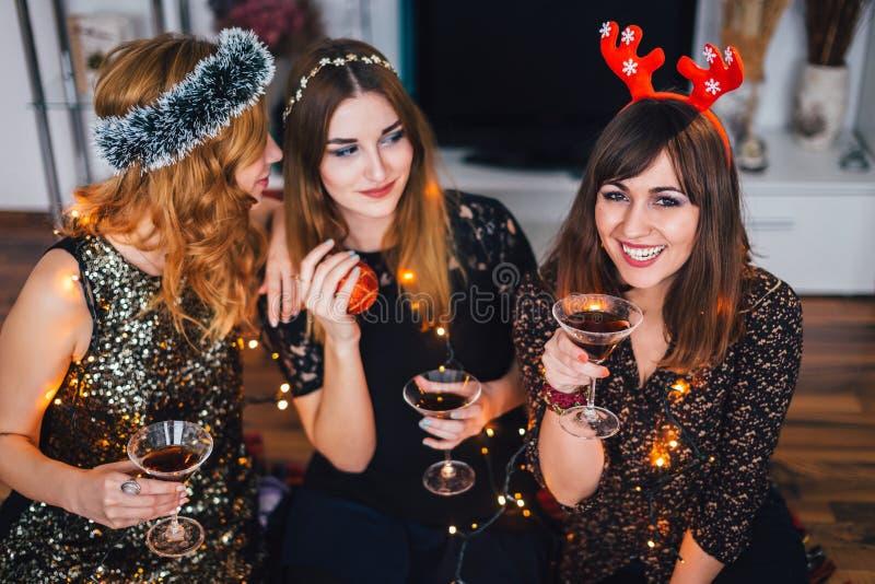 Três menina em uma festa de Natal home, um someth de sussurro da menina fotos de stock royalty free