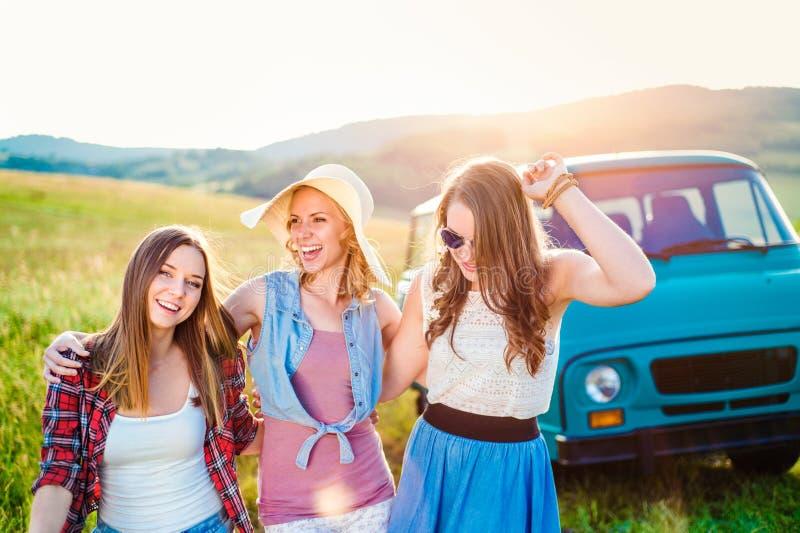 Três meninas adolescentes do moderno em um roadtrip, dia de verão imagem de stock royalty free