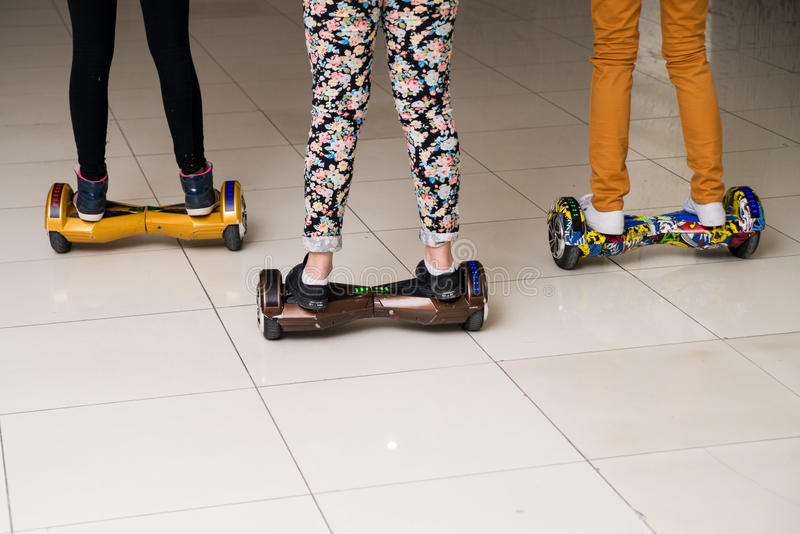 Três meninas adolescentes montam nos pés do gyrometer perto acima fotografia de stock