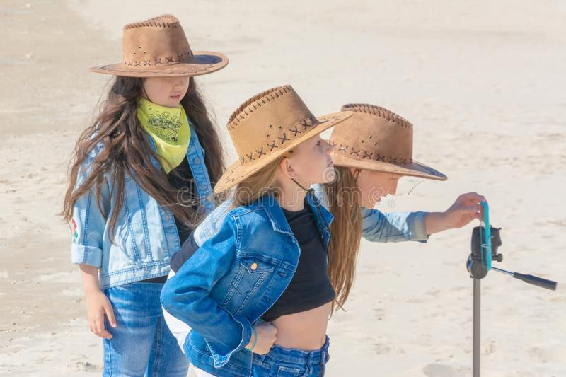 Três meninas adolescentes tomam um selfie em um telefone em um dia ensolarado fotografia de stock