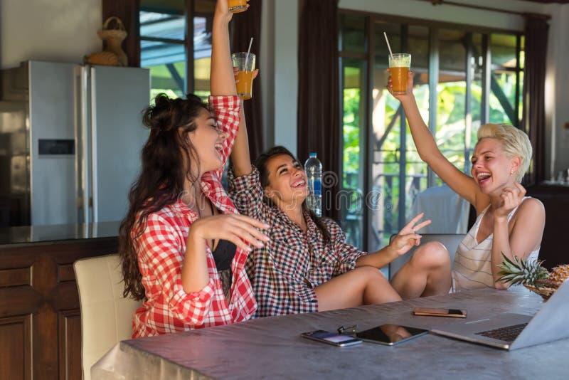 Três meninas alegres que sentam-se na tabela nas mãos levantadas de sorriso felizes da cozinha que guardam o suco de laranja, pos foto de stock