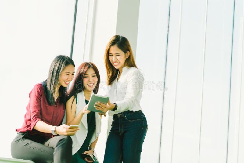 Três meninas asiáticas bonitas que usam a tabuleta digital junto Mulher ou estudantes universitário de funcionamento que conversa imagens de stock