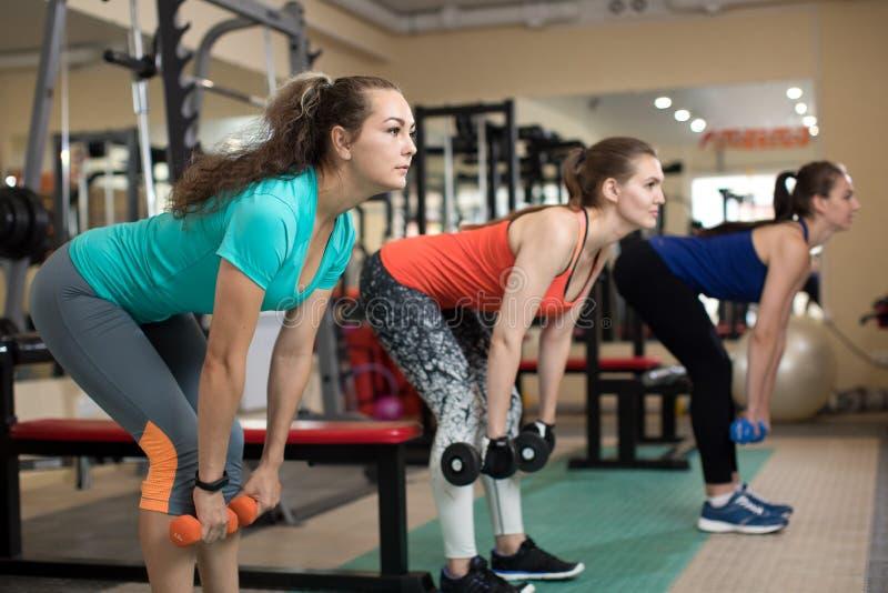 Três meninas ativas da aptidão nova que fazem exercícios com kettlebells no gym imagens de stock