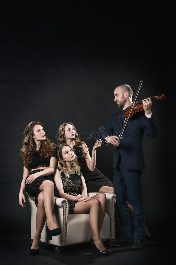 Três meninas bonitas em vestidos de nivelamento pretos estão sentando-se na cadeira, e o homem joga o violino foto de stock royalty free