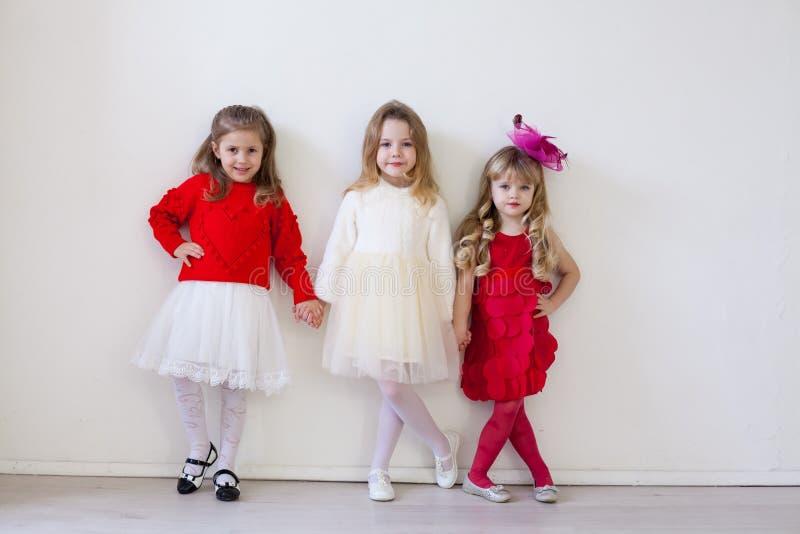 Três meninas bonitas pequenas nas mãos vermelhas da posse fotografia de stock royalty free