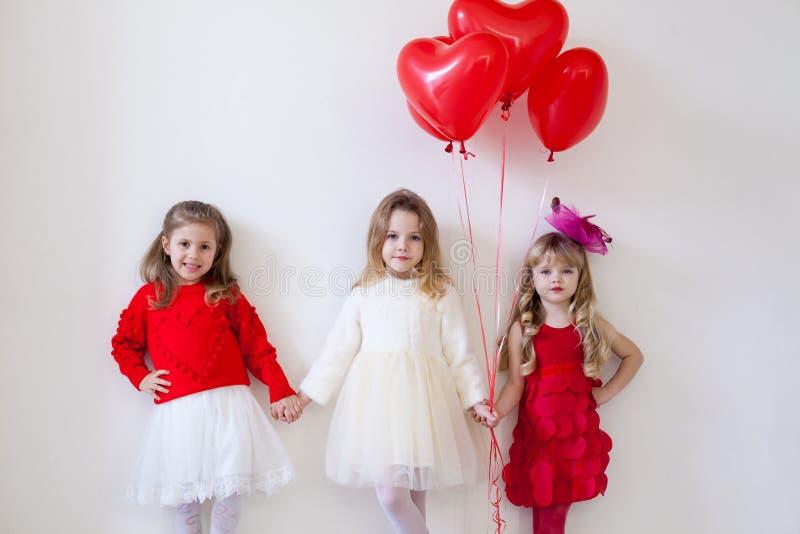 Três meninas bonitas pequenas nas mãos vermelhas da posse imagem de stock royalty free