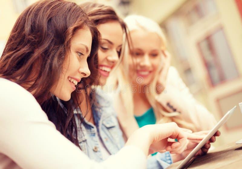 Três meninas bonitas que olham o PC da tabuleta no café imagens de stock royalty free