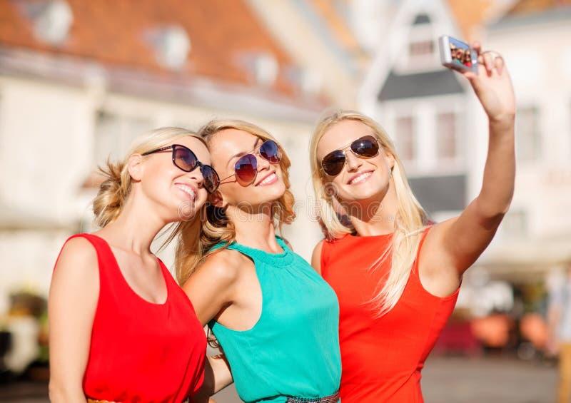 Três meninas bonitas que tomam a imagem na cidade fotos de stock royalty free