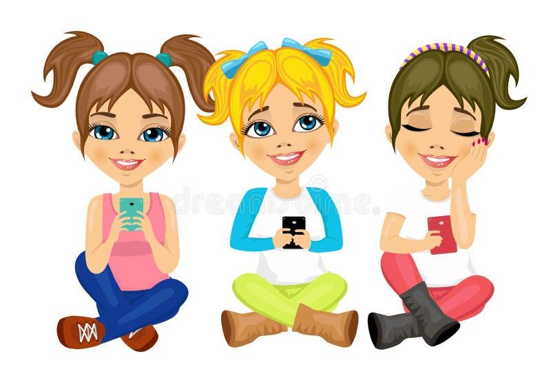 Três meninas bonitos que sentam-se no assoalho usando seu sorriso dos smartphones feliz ilustração stock