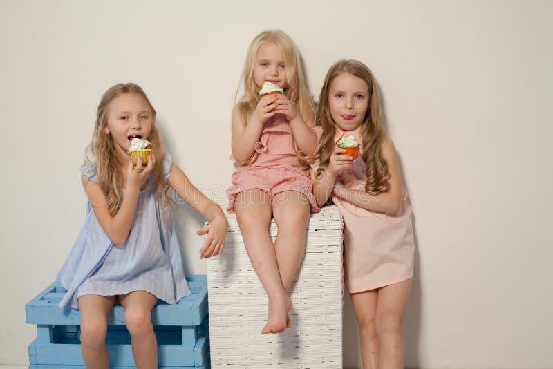 Três meninas comem o bolo doce com queque de creme imagens de stock royalty free