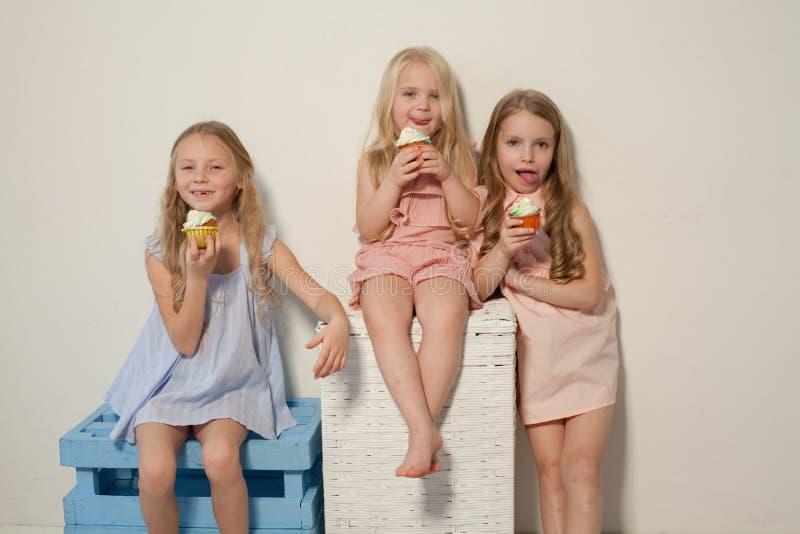 Três meninas comem o bolo doce com queque de creme foto de stock royalty free