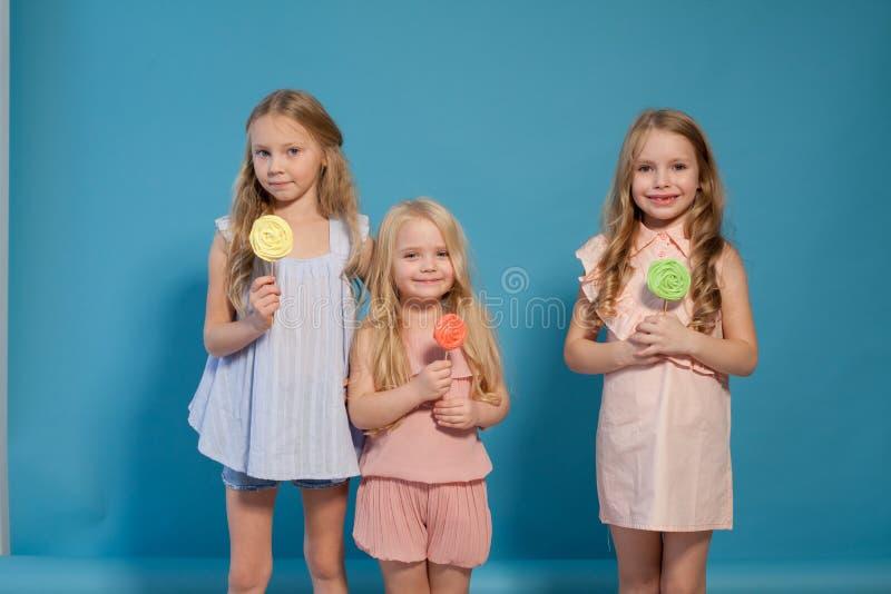 Três meninas comem o pirulito doce dos doces imagens de stock