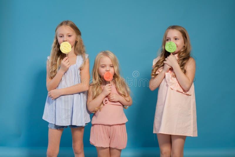 Três meninas comem o pirulito doce dos doces imagem de stock