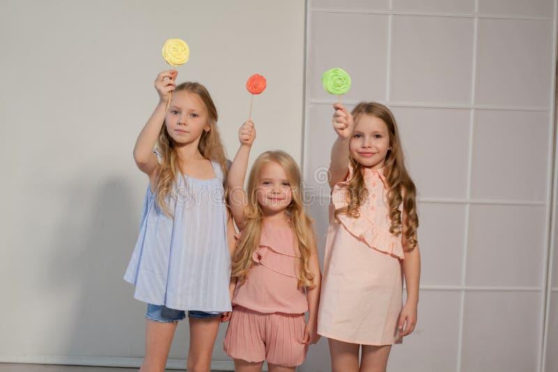 Três meninas comem o pirulito doce dos doces fotos de stock
