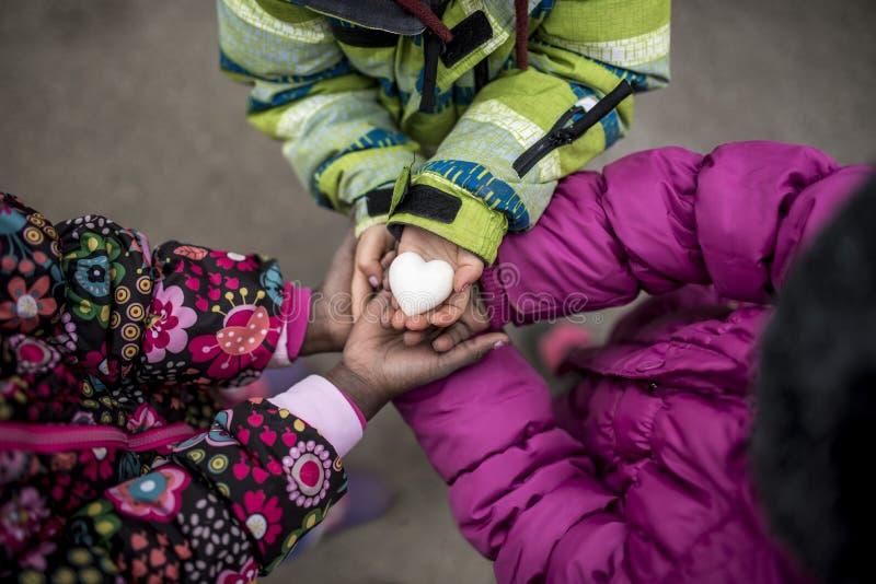 Três meninas da criança que guardam suas mãos juntaram-se junto com foto de stock