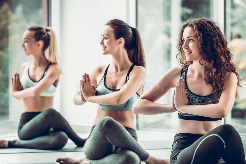 Três meninas da ioga no fundo da classe da aptidão imagens de stock royalty free