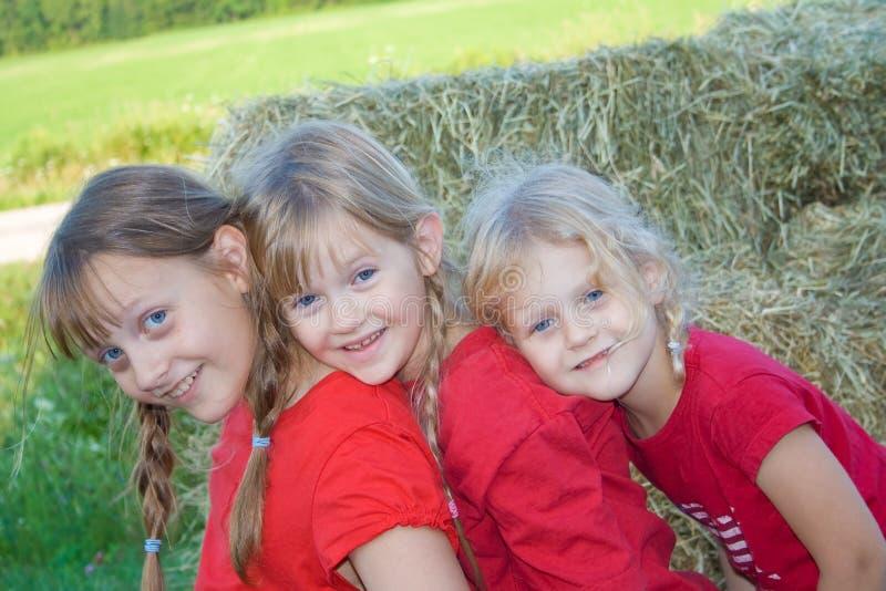 Três meninas de exploração agrícola felizes. foto de stock