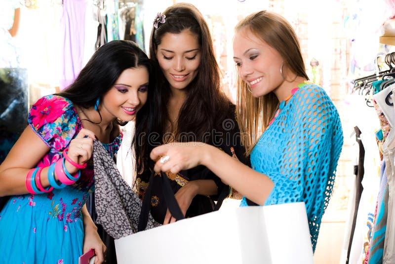 Três meninas de sorriso estão comprando imagem de stock royalty free