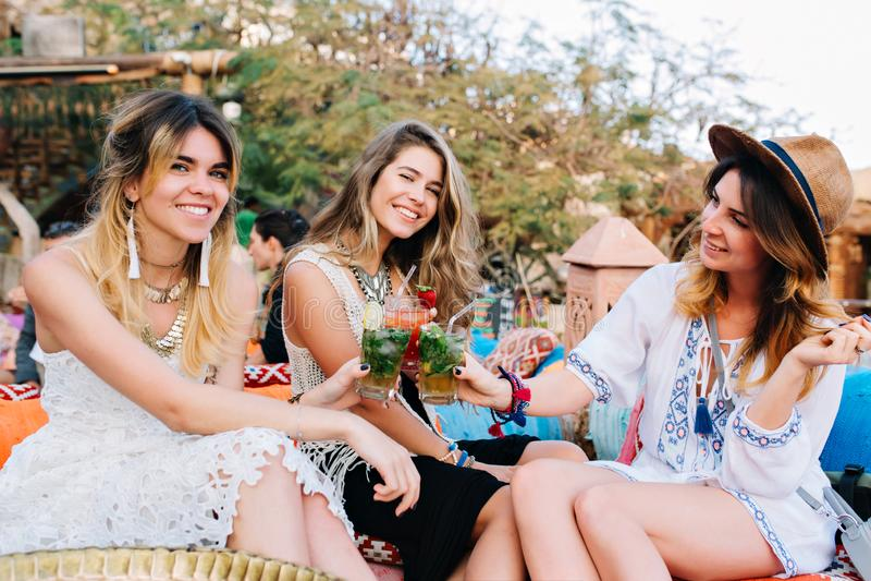 Três meninas de surpresa na roupa à moda do vintage que tem o divertimento no café exterior e que bebe cocktail Grupo de amigos imagens de stock royalty free