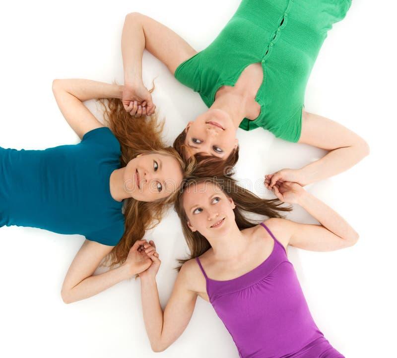Três meninas do coquette que prendem as mãos imagem de stock