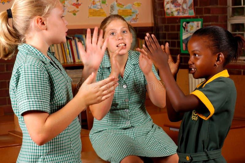 Três meninas elementares que jogam jogos fotografia de stock