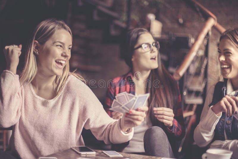 Três meninas em casa que jogam cartões imagem de stock royalty free