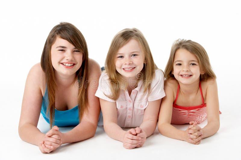 Três meninas empilhadas acima na pirâmide no estúdio foto de stock