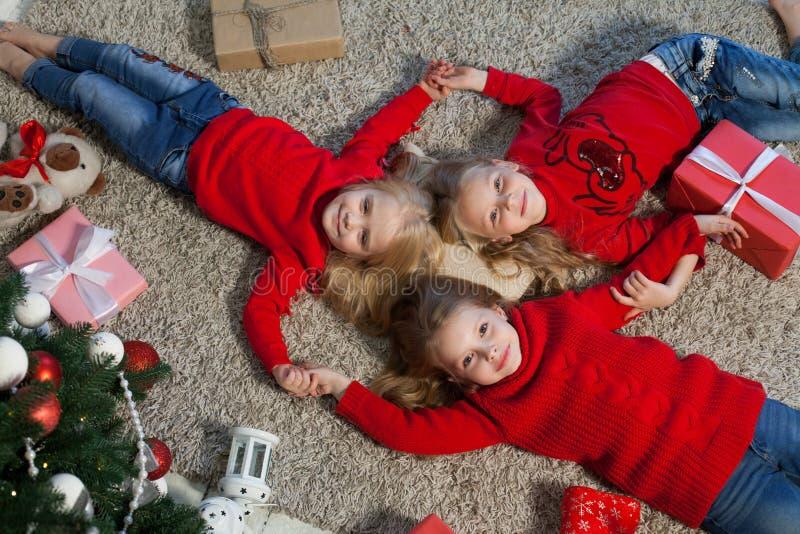 Três meninas encontram-se perto de uma árvore de Natal com feriado do ano novo dos presentes fotos de stock