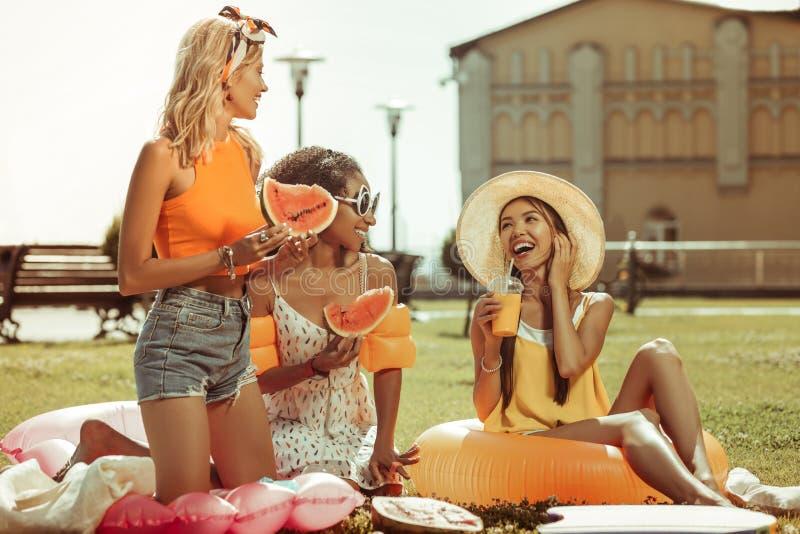 Três meninas felizes alegres que têm um piquenique com frutos fora imagens de stock