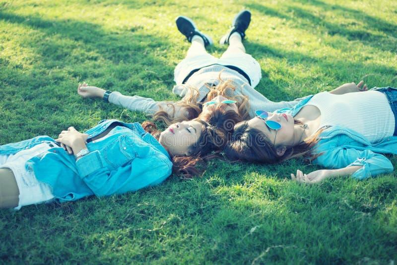Três meninas felizes de Ásia que encontram-se na grama verde nos óculos de sol foto de stock royalty free