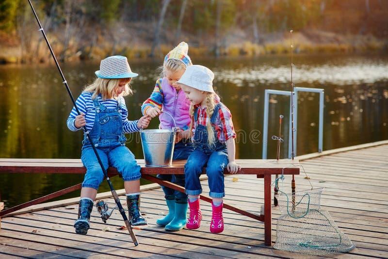 Três meninas felizes pequenas vangloriam-se sobre os peixes travados em um polo de pesca Pesca de um pontão de madeira imagens de stock royalty free
