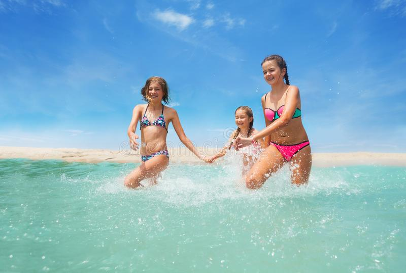 Três meninas felizes que correm no espirro do mar fotografia de stock royalty free